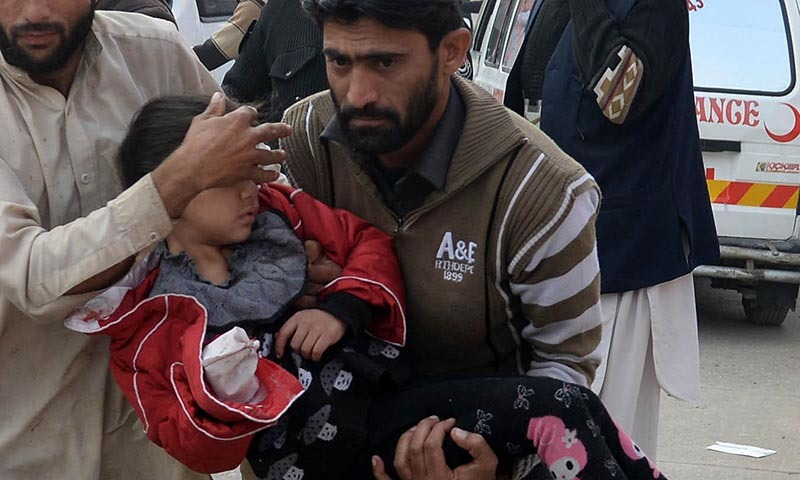 Men carry an injured school girl to a hospital following an attack by Taliban gunmen on a school in Peshawar on December 16, 2014. — AFP