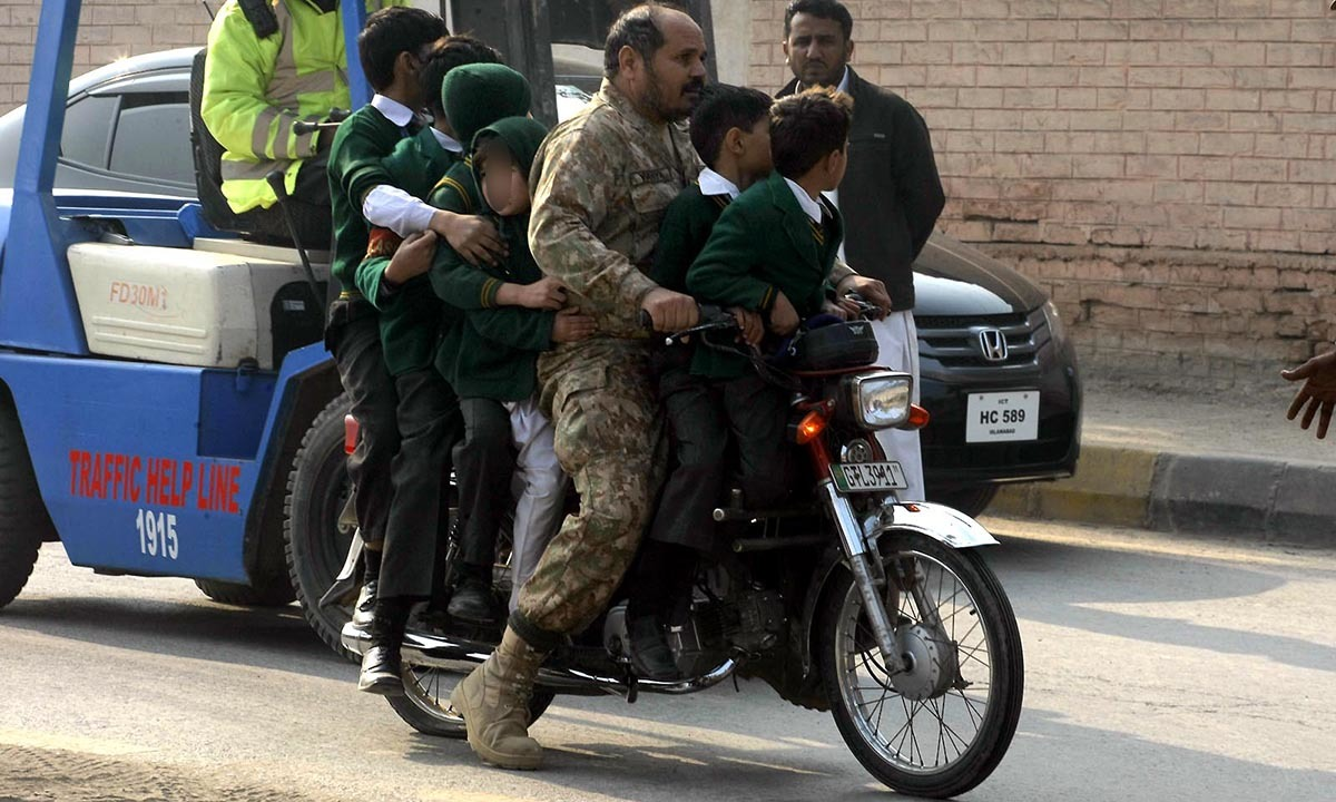 Army personnel shifting the school children on motorbike following the TTP attack on Army Public School situated on Warsak Road. — INP