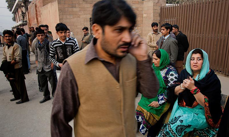 People wait for their children outside a school attacked by the Taliban in Peshawar. -AP Photo