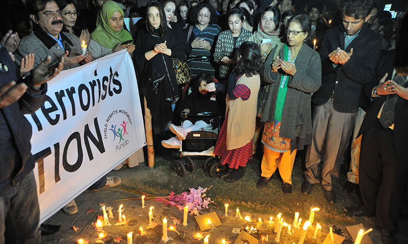 Asma Jahangir and other civil society activist praying during candle vigil for people who died in Peshawar incident. — INP