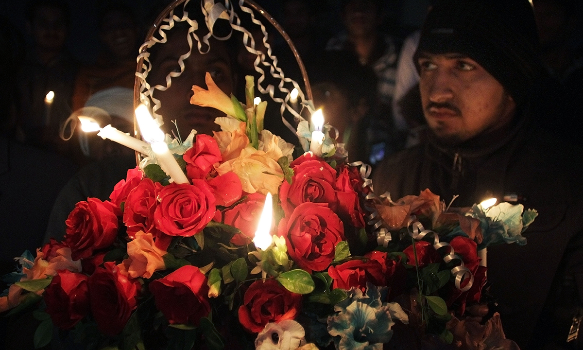 Activists of a religious group's student wing hold a flower basket and candles. — AP