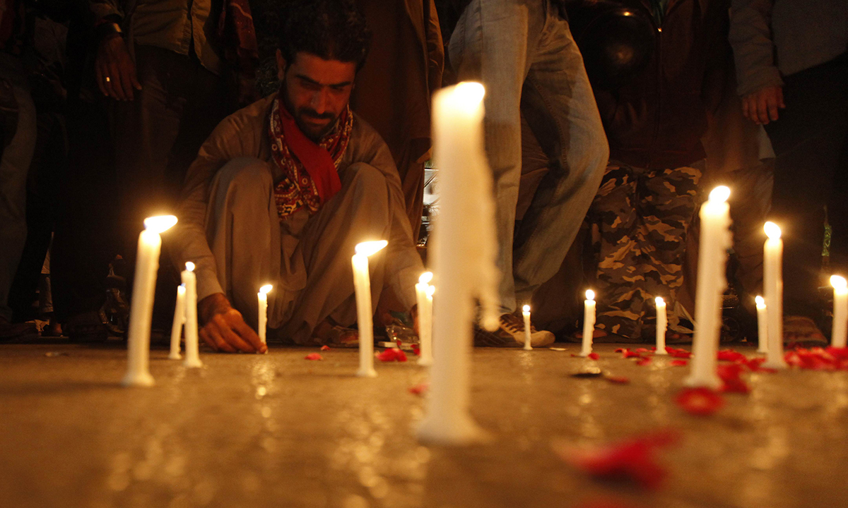 A man lights candles to mourn victims from Army Public School in Peshawar. — Reuters