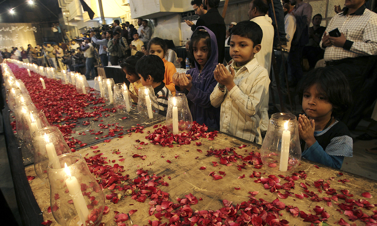 Children pray for the departed school children in Peshawar. — AP
