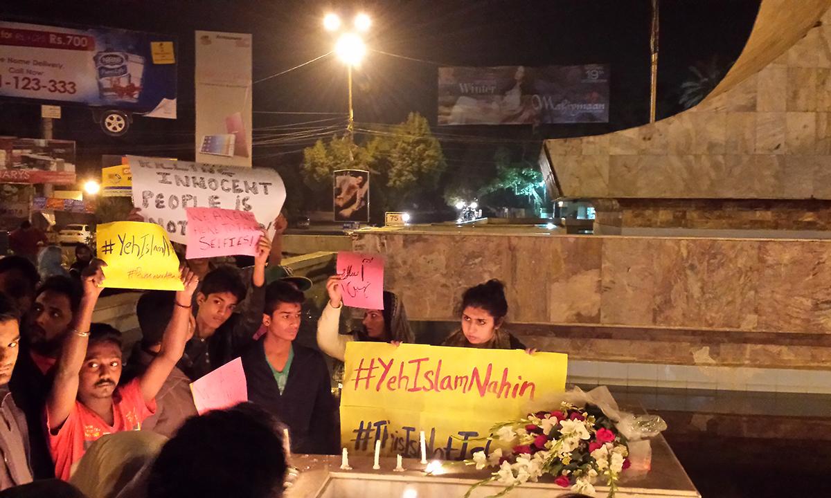 People partake in a candle light vigil at Teen Talwar, Clifton, Karachi. — Ali Umair Jaffery