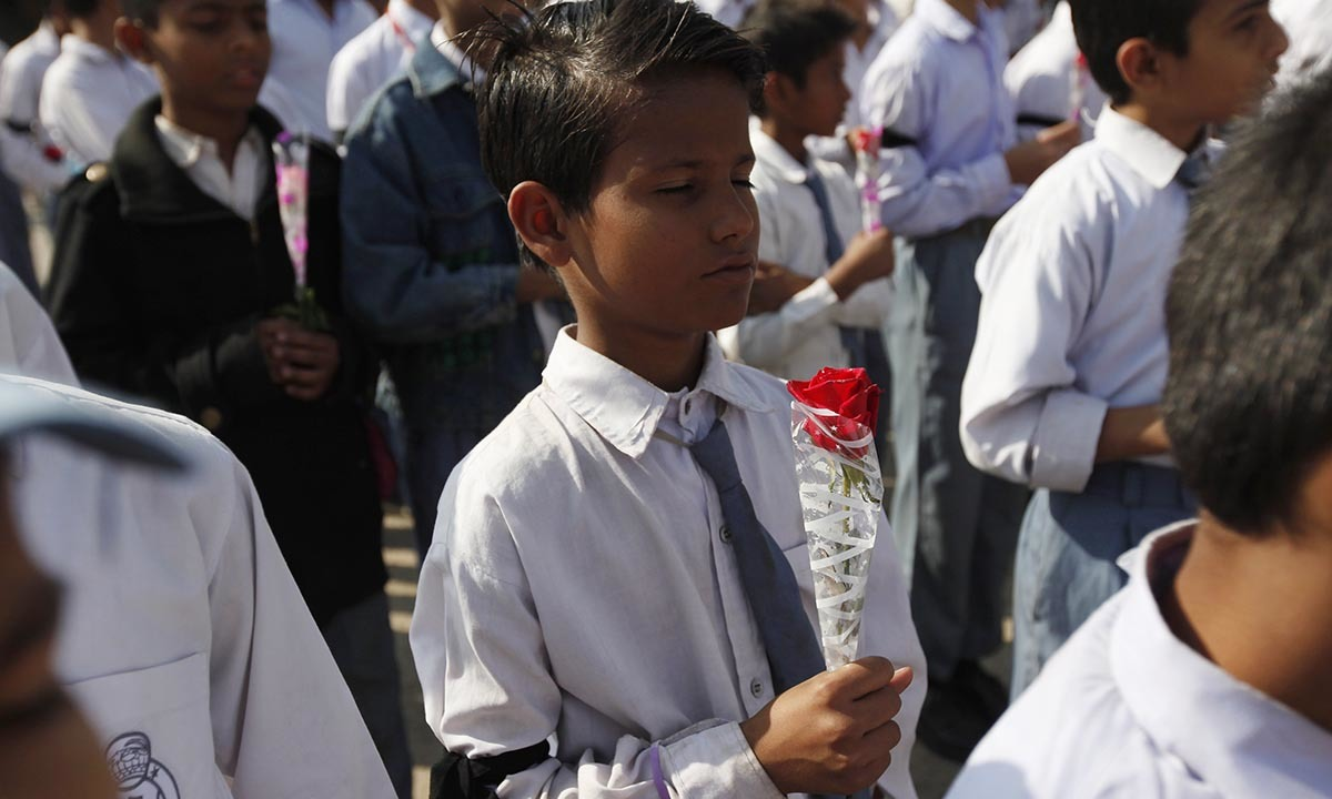 A student, wearing a black ribbon and holding a rose, takes part in a prayer for victims of the Taliban attack on the Army Public School in Peshawar, in Karachi, December 17, 2014. — Reuters