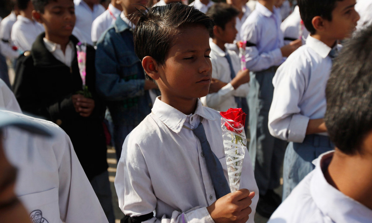 A student in Karachi holding a rose takes part in a prayer for victims of the Taliban attack on Army Public School in Peshawar. – Reuters