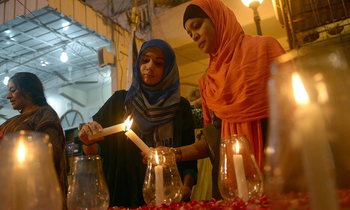 Activists light candles. — AFP
