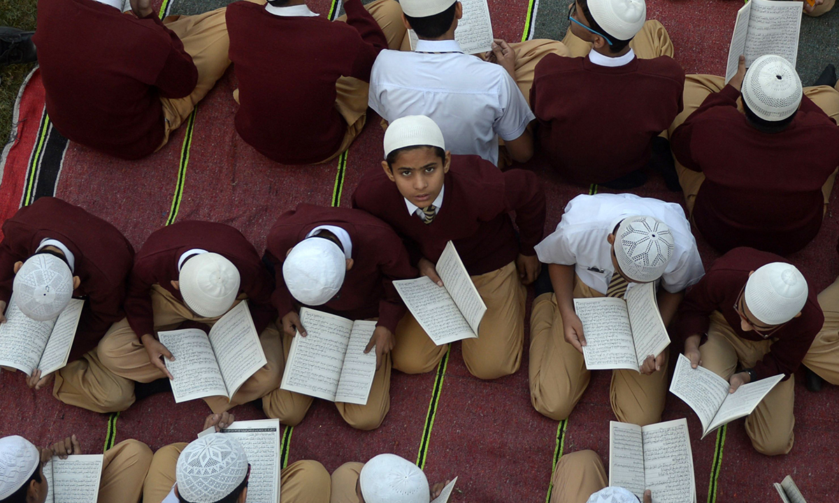 Students in Karachi read the Holy Quran and pray for the victims. — AFP