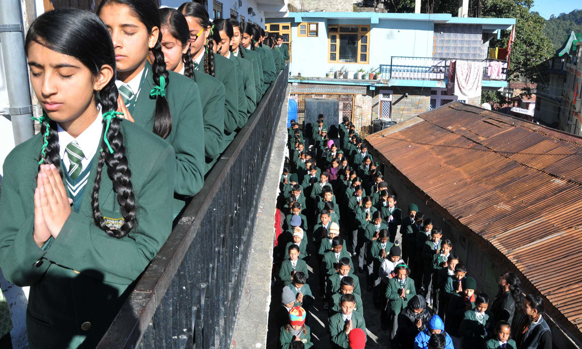 Schoolchildren pray during morning assembly at their school in Shimla. – AFP