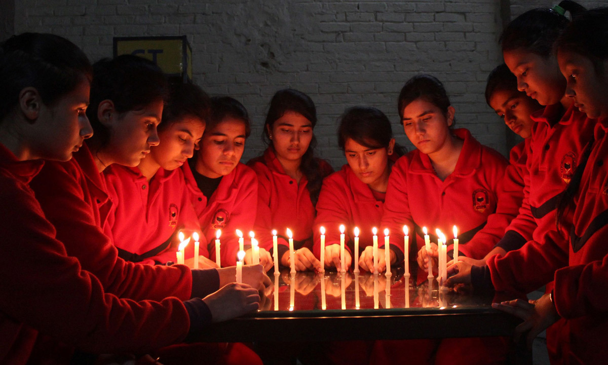 Indian schoolchildren prepare lighted candles ahead of a vigil in the northern city of Jalandhar, India. – AFP