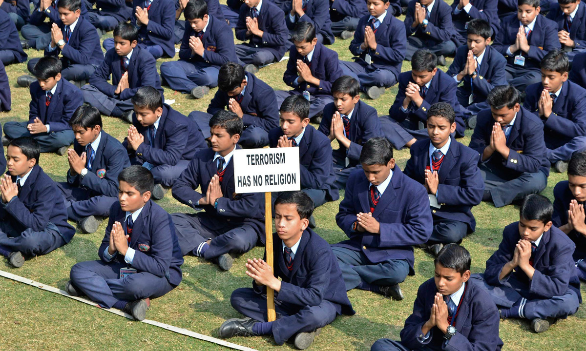 Schoolchildren take part in a prayer for victims of the Taliban attack on the Army Public School in Peshawar, in the northern Indian city of Mathura. — Reuters