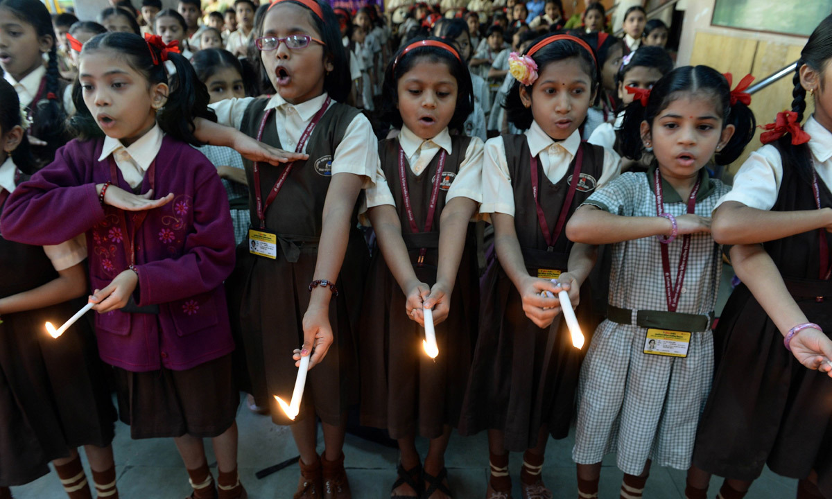 Schoolchildren take an oath as they hold lighted candles at their school in Mumbai. — AFP