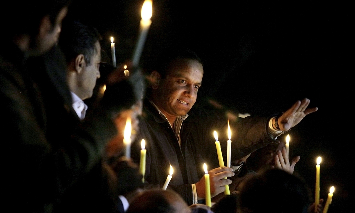 Pakistani journalists and civil society members hold a candle light vigil. — AP