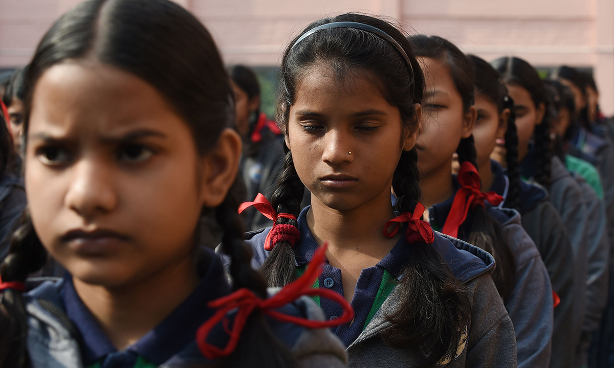 Schoolchildren pray during an assembly at their school in New Delhi. — AFP