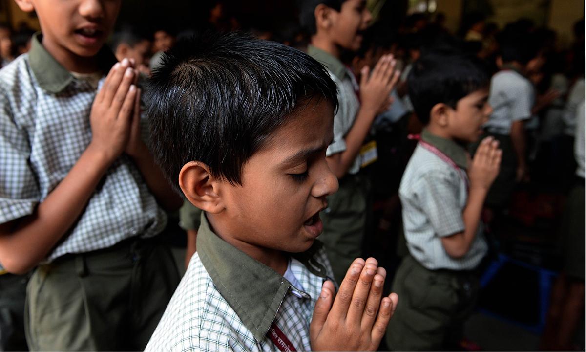 Indian schoolchildren pray at their school in Mumbai. — AFP