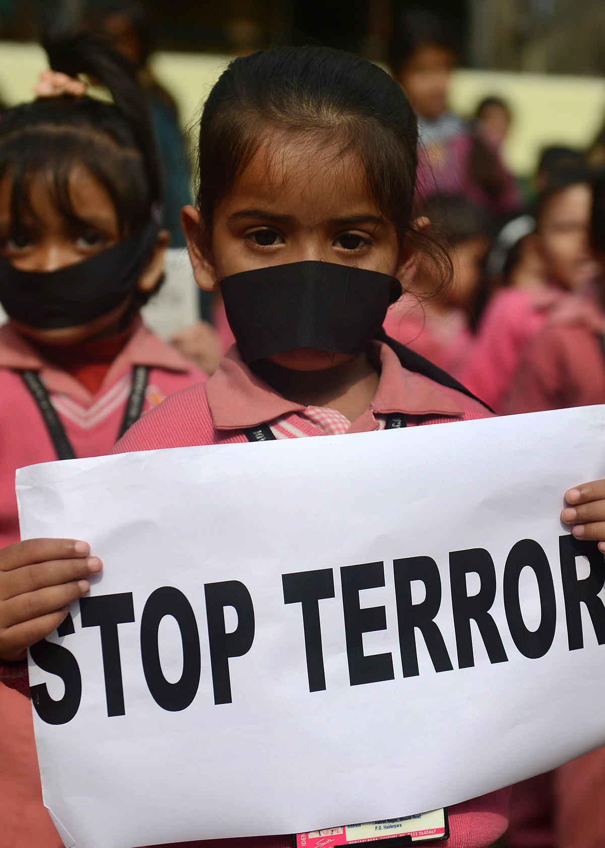 Children hold placards as they pay tribute to Pakistani children and staff in the attack in Peshawar, during morning assembly at their school in Siliguri. — AFP