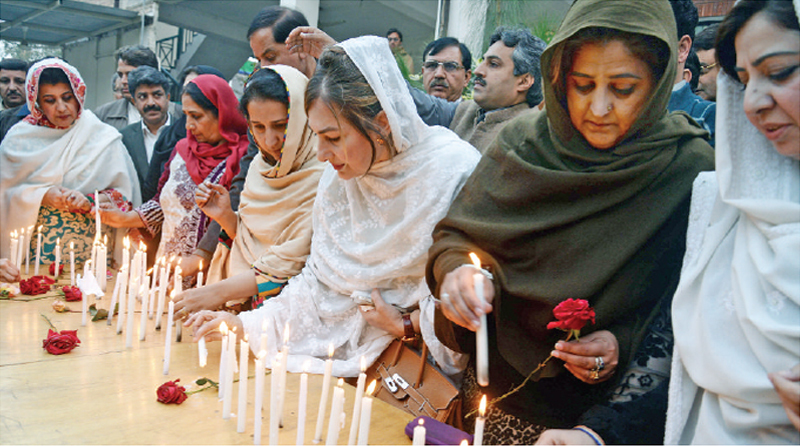 WOMEN leaders of political parties members of civil society hold a candle light vigil in Peshawar. — White Star