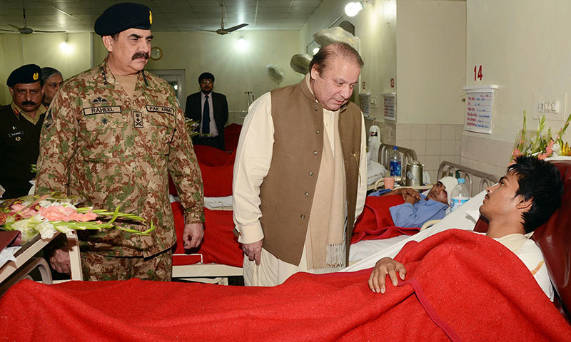 This handout picture released by Inter-Services Public Relation (ISPR) on December 17, 2014 shows Prime Minister Nawaz Sharif (C) chatting with an injured student from the Army Public School a day after militants attacked the school, at the military hospital in Peshawar, as army chief General Raheel Sharif (L) looks on. — AFP