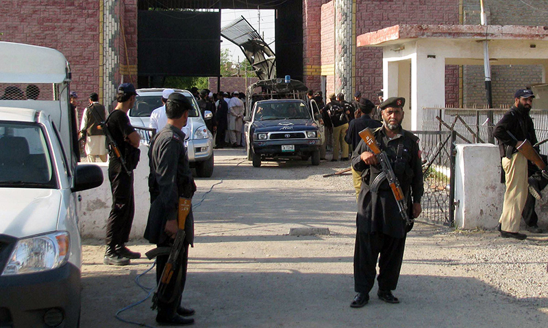 In this photo, security officials gather at the damaged main entrance of a prison following an attack by armed militants in Bannu on April 15, 2012. — AFP/File