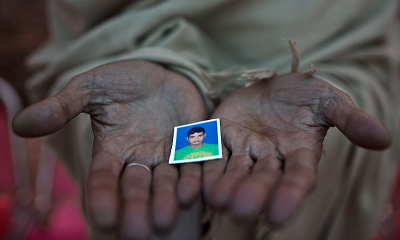 Sayed Shah, shows a picture of his son Zulqarnain, 17, a student who was killed in last Tuesday's Taliban attack on the Army Public School in Peshawar. —AP