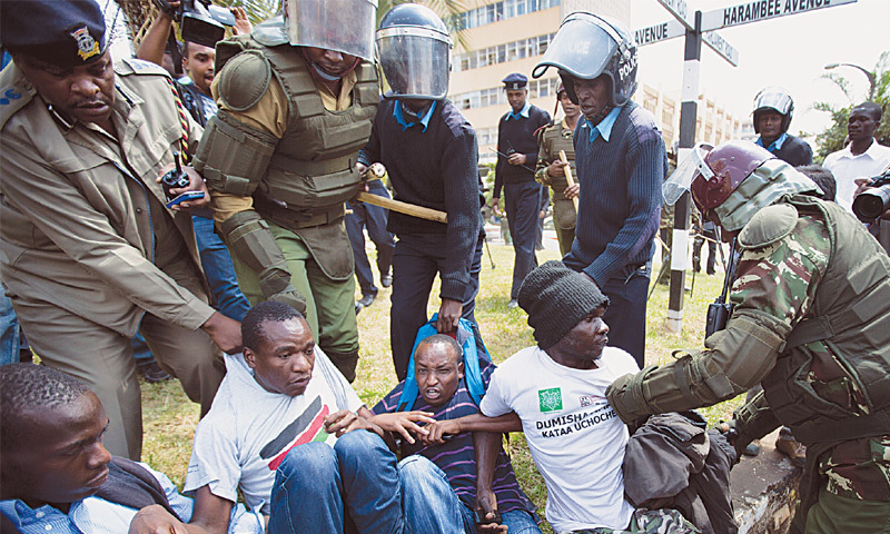 Nairobi: A group of protesters against the new security law, who managed to get past heavy police cordons preventing demonstrations, are beaten with wooden clubs and arrested by riot police after shouting against the new law, outside the Parliament building on Thursday.—AP