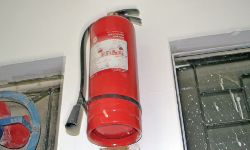 An outdated fire extinguisher hangs on a wall at Islamabad Model College for Boys, G-10.