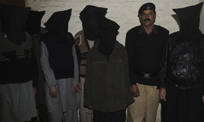 A police officer stands with alleged militants, who stand hooded in police custody in Lahore.— AP/file