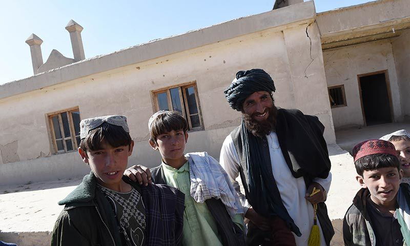 Bismillah (2R), the current mullah at the mosque where Mullah Omar founded the Taliban movement 20 years ago, stands in front of the mosque along with his sons in the village of Sangesar. — AFP