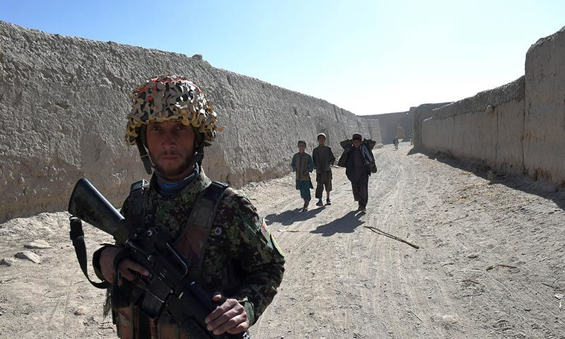 An Afghan National Army soldier is followed by three village boys while walking in the compound of the mosque where Mullah Omar founded the Taliban movement 20 years ago. — AFP