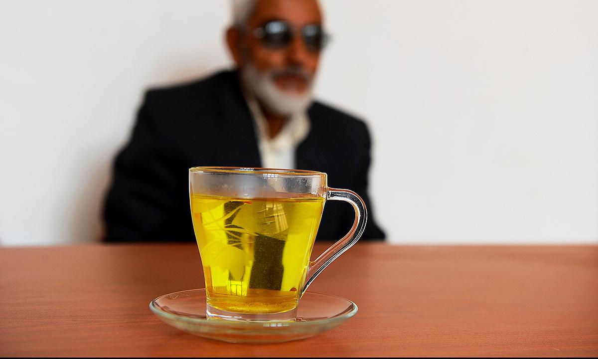 A resident sits alongside a saffron drink. - AFP