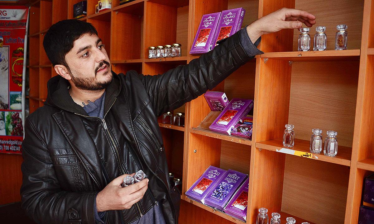 Saffron seller arranges items at his shop. - AFP