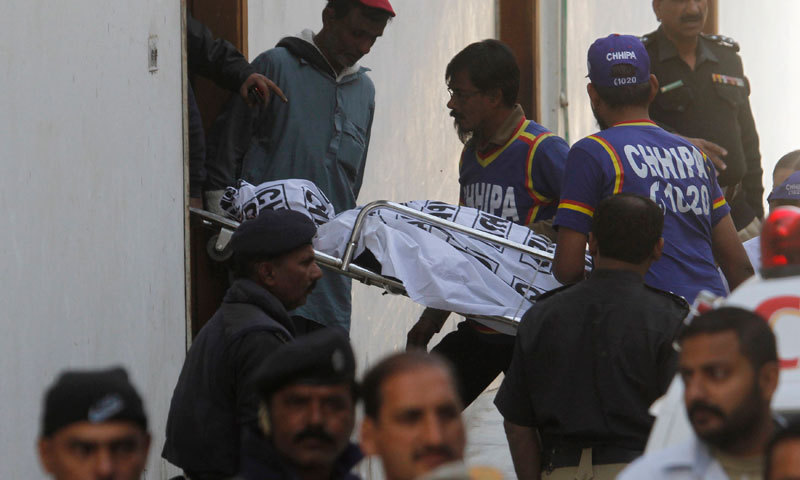 The image shows men shifting a body.—Reuters/File
