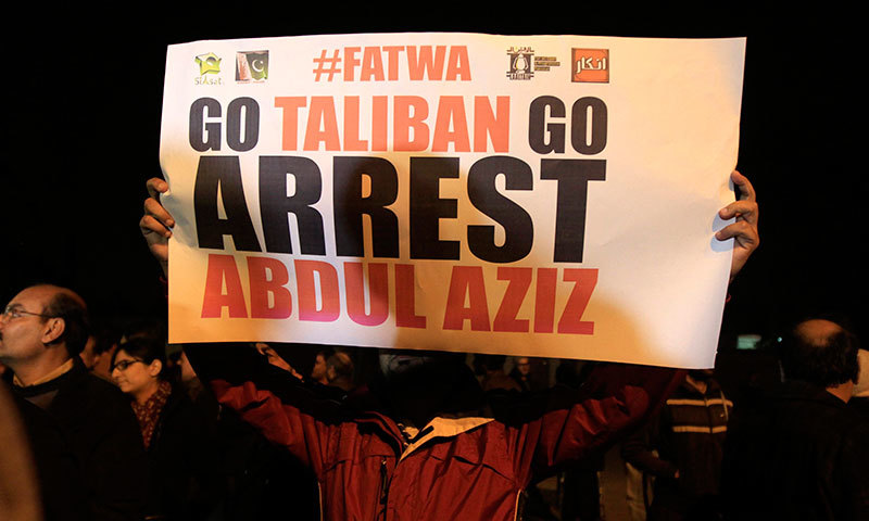 A man holds a sign during a protest near Lal Masjid in Islamabad, December 19, 2014. - Reuters