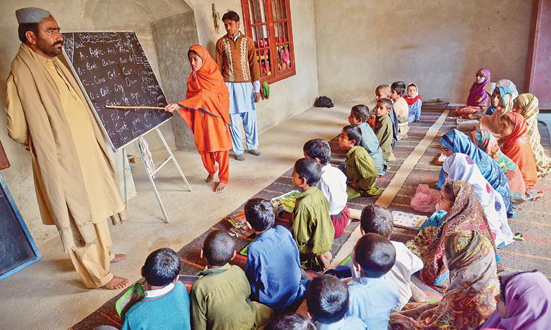 Bandit Jam Khan Sundrani stands inside a class of a makeshift school on the floodplain bordering Ghotki.—Fahim Siddiqi / White Star