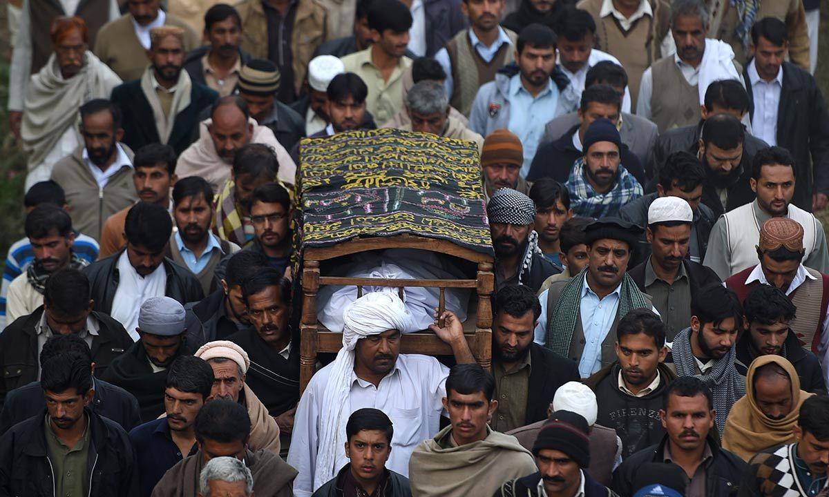 People carrying the body of Arshad Mehmood for his burial in Javera village. -AFP Photo