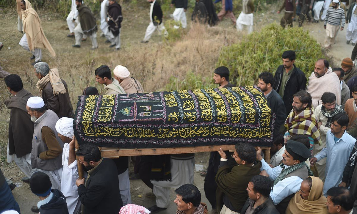 People carrying the body of executed militant Arshad Mehmood to his burial site. -AFP Photo