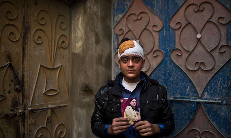 Pakistani student Mohammad Baqair, who survived last Tuesday's Taliban attack on a military-run school and was slightly injured, poses for a picture holding a photograph of his mother a victim of the attack, who was a teacher at the school, at his home, in Peshawar. - AP
