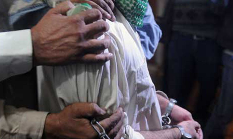 Policemen escort a suspected militant of Tehrik-e-Taliban Pakistan.—AFP/File