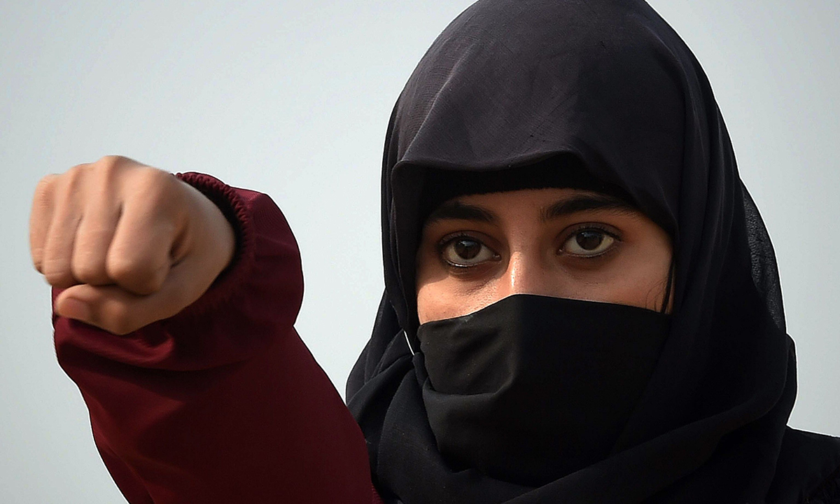 A female police commando demonstrating her skills at a police training centre in Nowshera. — AFP