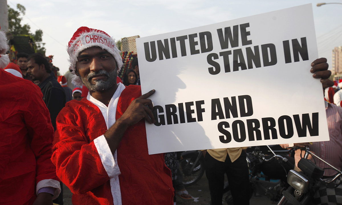 A man in a Santa Claus outfit holds a sign in support of the victims of the Peshawar attack, during a rally in Karachi. — Reuters