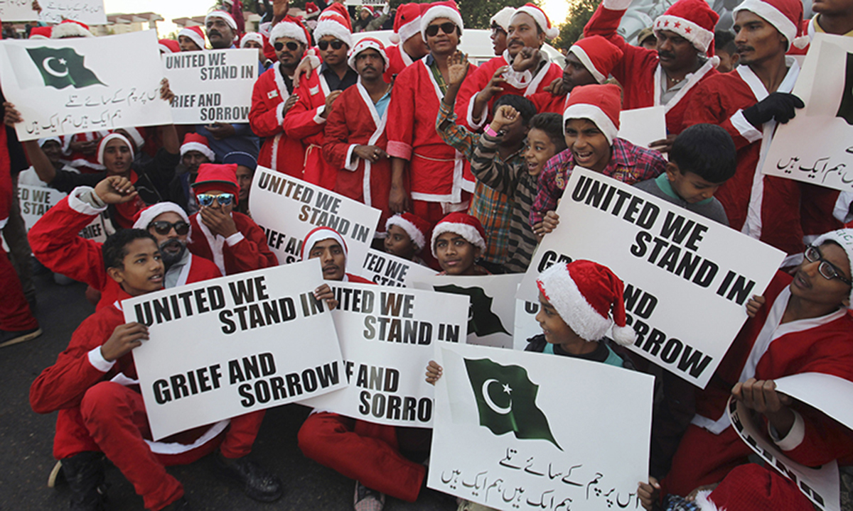 Christians dressed as Santa Claus condemn Taliban attack on the school in Peshawar. — AP
