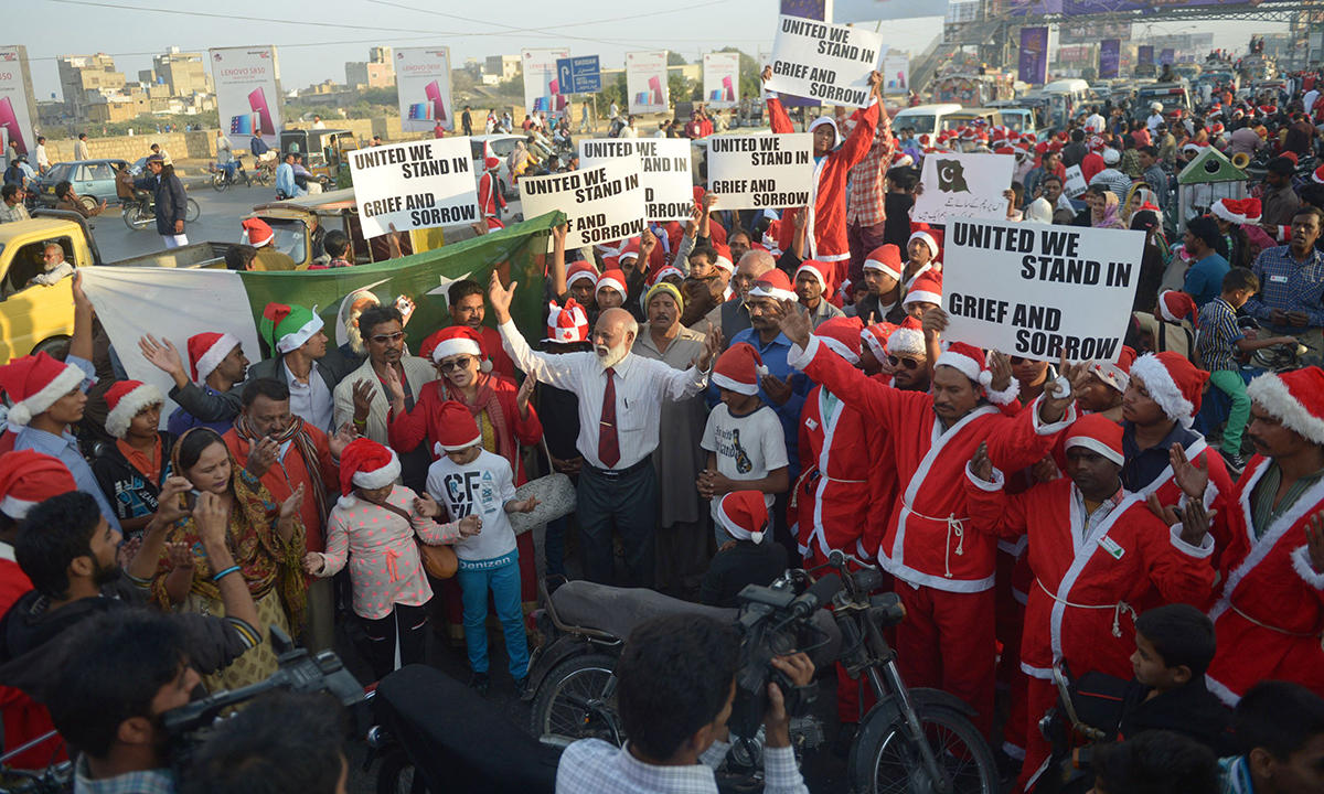 People gather to protest against the attack in Peshawar. — AFP