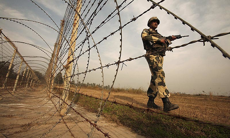 An Indian Border Security Force (BSF) soldier patrols near the fenced border with Pakistan.  — Reuters/file