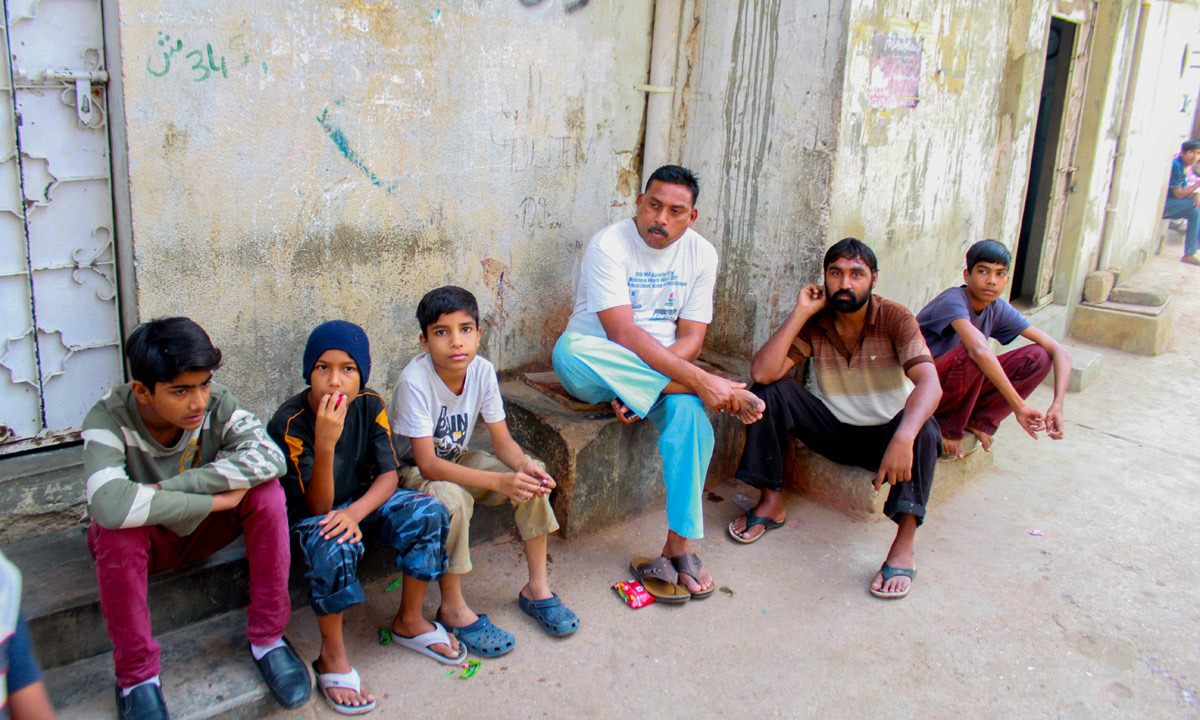 Men sit at the corner of a street in Essa Nagri. Unemployment and illiteracy is high in the area. — Umer Sheikh