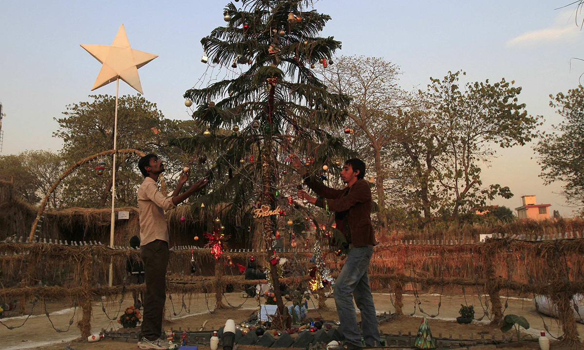 Men decorate a Christmas tree. — Reuters