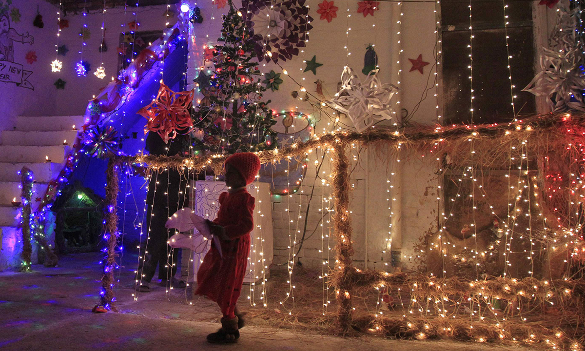 A girl stands outside a house illuminated with lights on Christmas Eve. — Reuters