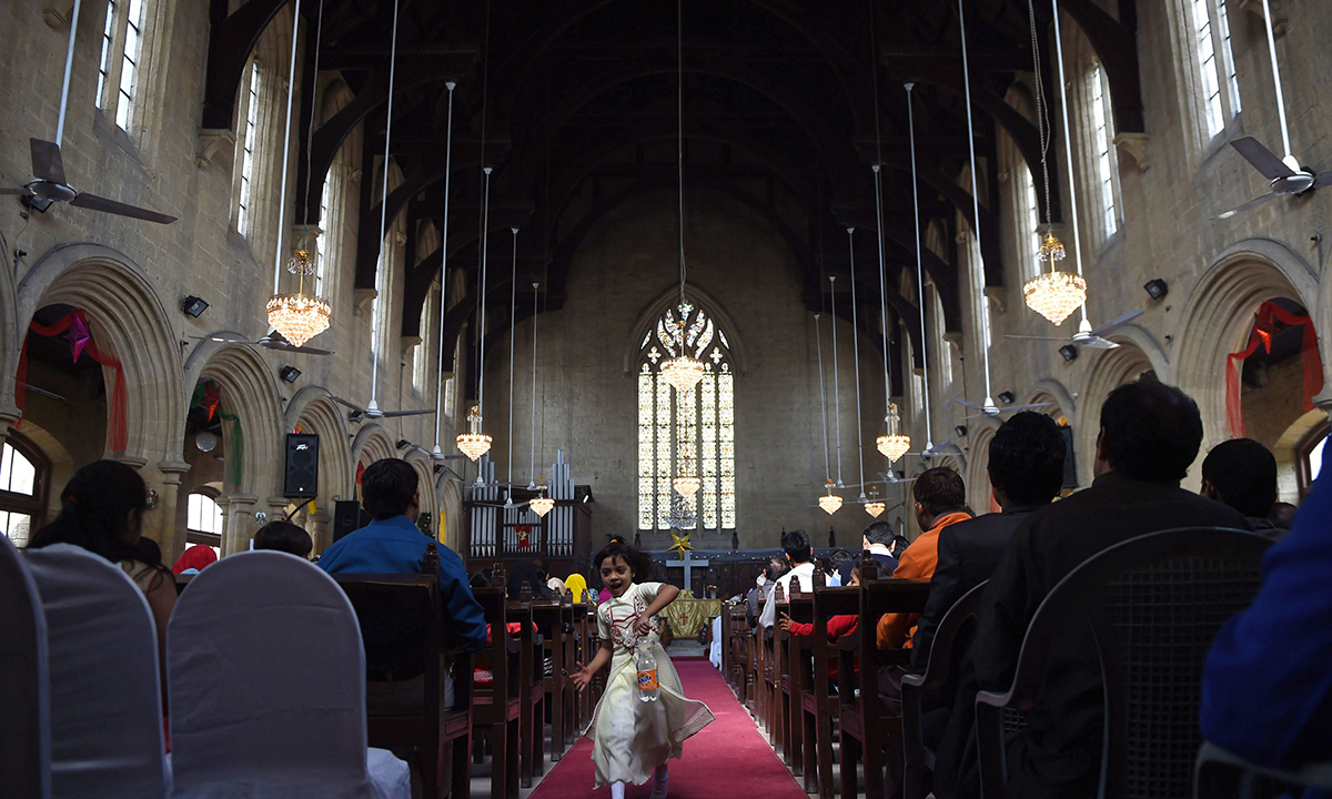 A girl runs down the aisle in a Christmas mass at St. Patrick's Cathedral in Karachi. — AFP