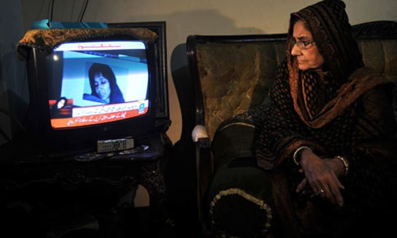 Ismat Siddiqui, the mother of US-detained Pakistani woman Aafia Siddiqui, watches a news channel after a court verdict in Karachi. — AFP/File