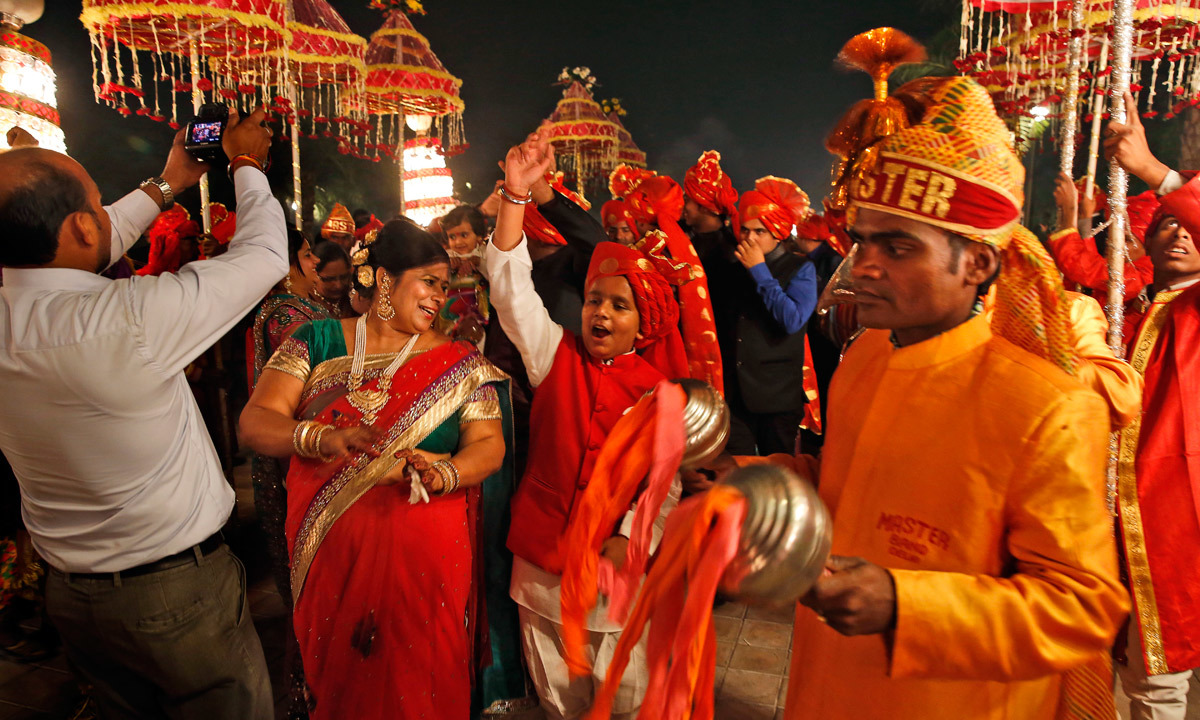 Members Of Indian Brass Band Play As They Accompany A Wedding Procession In New