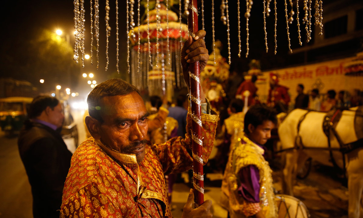 A Member Of Indian Brass Band Holds Decorative Lights As He Accompanies Wedding Procession